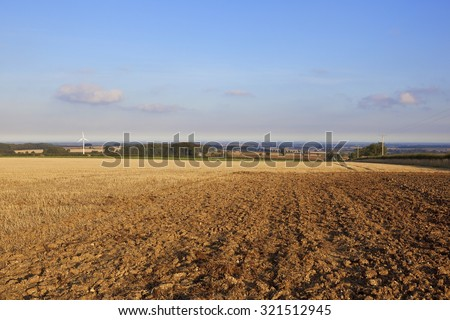 a harvested wheat field with wind turbine on the yorkshire wolds england with a view of the vale of york under a blue sky in autumn - stock photo