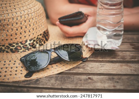 A hat and a pair of sunglasses on a table outside with a woman in the background - stock photo