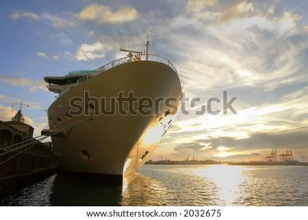 A Hawaiian cruise ship or liner docked near the Aloha Tower at sunset - stock photo