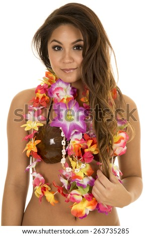 A Hawaiian woman in her coconut bra with her lei around her neck with a small smile. - stock photo