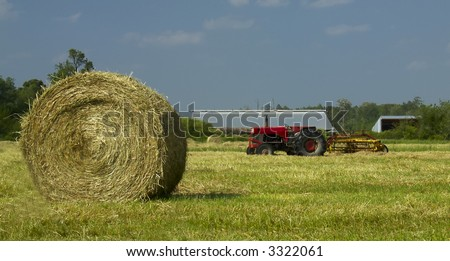 A hay bale and red tractor sit in a freshly mowed field