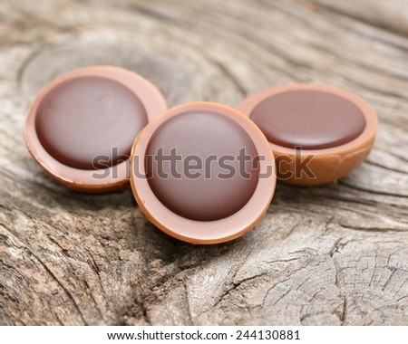 A hazelnut in caramel with creamy nougat and chocolate on wooden background - stock photo