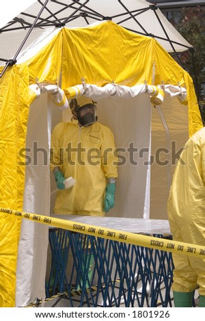 A hazmat crew member awaiting a victim in a decontamination shower. - stock photo