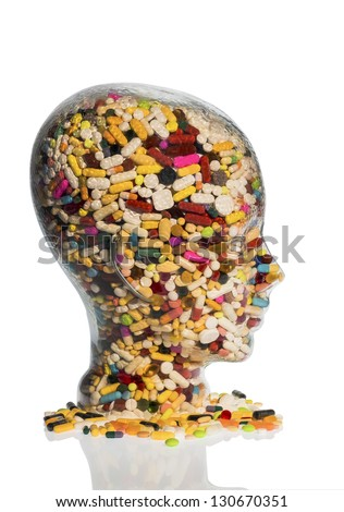 a head made of glass filled with many tablets. photo icon for drugs abuse and addiction tablets. - stock photo