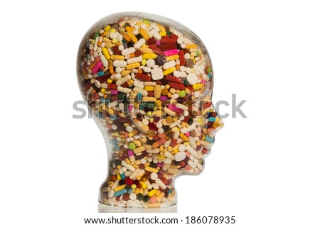a head made of glass filled with many tablets. photo icon for drugs, abuse and addiction tablets. - stock photo