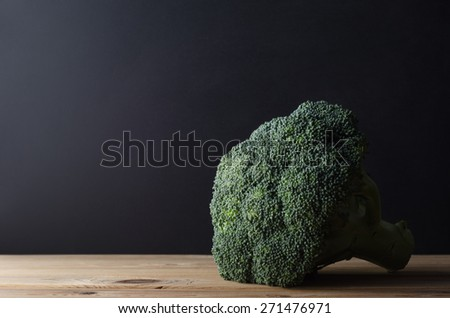 A head of dark green broccoli with stalk intact, on wooden planked kitchen table against black chalkboard background.  Moody lighting. - stock photo