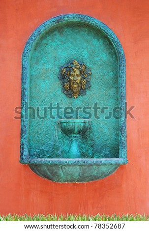 A head water fountain on red wall - stock photo