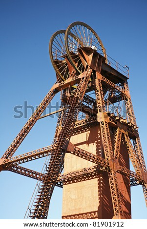 A headframe, winding tower, poppet head or pit head, is used in shaft mining to support the winding mechanism. The mine shaft is used to gain access to an underground mining facility. Australia. - stock photo