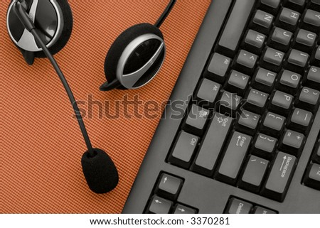 A headset and keyboard sit on a red desk - stock photo