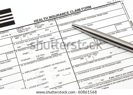 A health insurance claim form with a silver pen ready to be filled out for manual submission to an insurance carrier. - stock photo