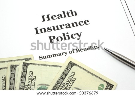 A health insurance policy with a pen ready for signing surround by cash in hundred dollar bills.