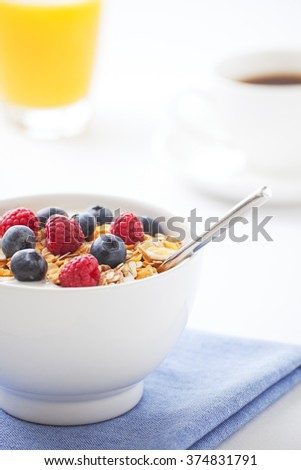 A healthy breakfast with muesli, fresh berries, orange juice and a cup of coffee. Shallow depth of field, focus on berries and muesli.