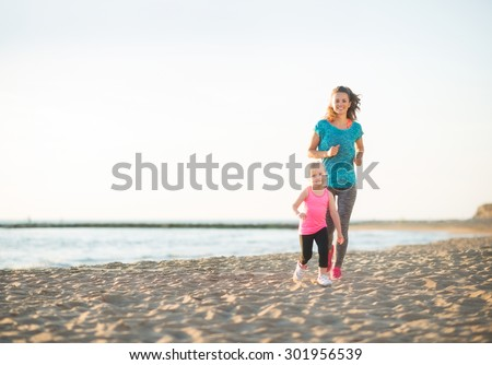 A healthy, fit mother and her young daughter are running together on the beach at sunset. The mother is behind her daughter, who feels like she is winning the race. - stock photo