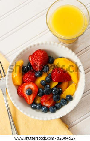 A healthy fresh fruit salad with strawberries, blueberries and nectarines is a delicious summer breakfast. - stock photo