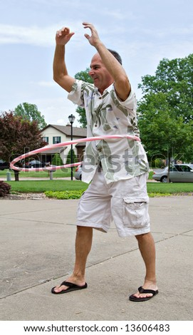 A healthy happy mature man plays with a hoola hoop. - stock photo