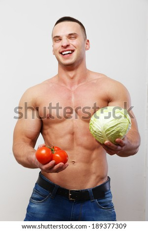 A healthy smiling guy with veggies