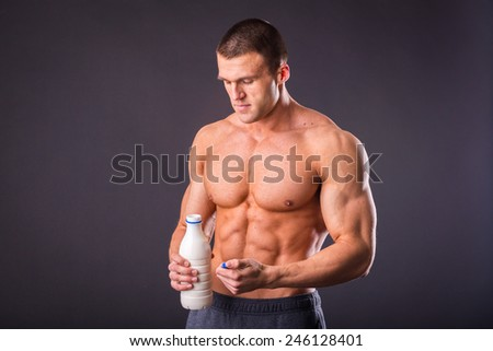 A healthy, strong man holding a bottle of milk. Concept of healthy food. Muscular man is going to drink milk.