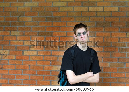 A healthy tall white male Caucasian student stands in front of a brick wall with his arms crossed with confidence. Background has lots of room for your text. - stock photo