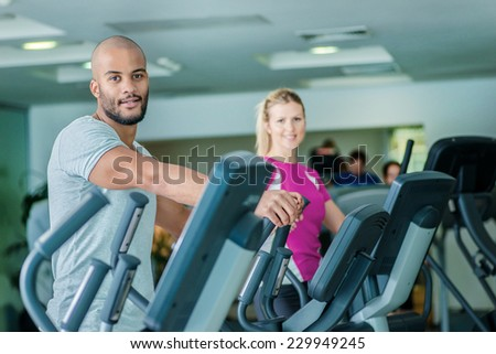 A healthy way of life. Two athletes engaged in the simulator and the gym at the camera. - stock photo