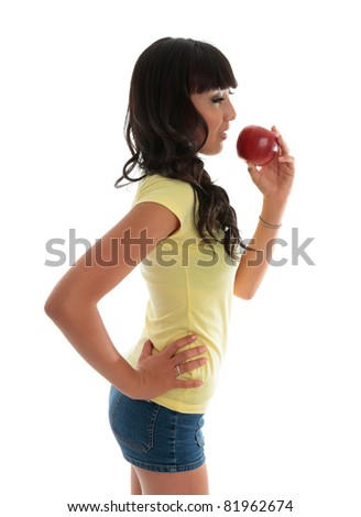 A healthy young woman eating a piece of fruit.  White background.