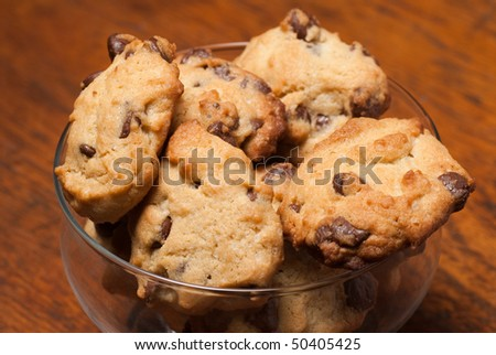 A heap of chocolate chip cookies against a wooden background - stock photo