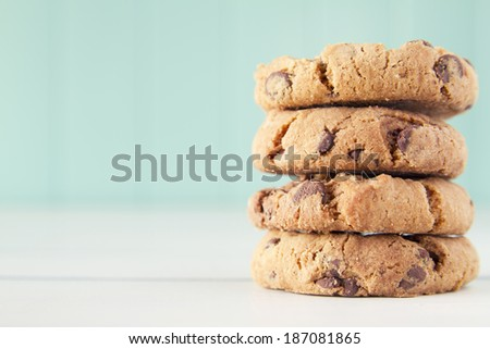 A heap of chocolate chip cookies on a white wooden table with a robin egg blue background. - stock photo