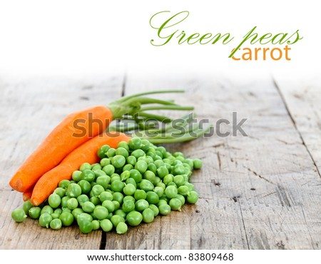 A heap of fresh green peas with carrots on it, place for your text up - stock photo