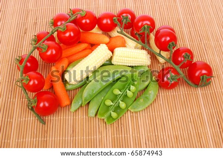 A heap of organic fresh and healthy red Mediterranean vine tomatoes, baby corn, sugar snap peas and chef style carrots. Image on bamboo studio background. - stock photo