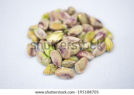 A heap of pistachio nuts on a white background on a sunny day. - stock photo