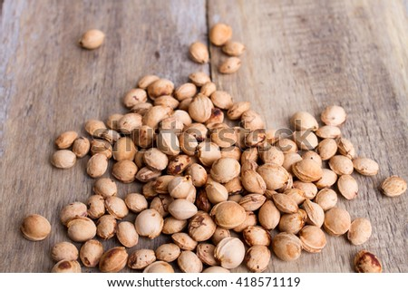 a heap of sour cherry pits on wood - stock photo