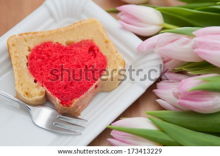 A heart cake for Valentines day with pink tulips - stock photo