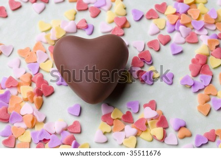 A heart chocolate with colorful samll ones scattered on the table