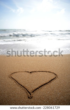 A heart drawn in the sand at the waters edge. - stock photo