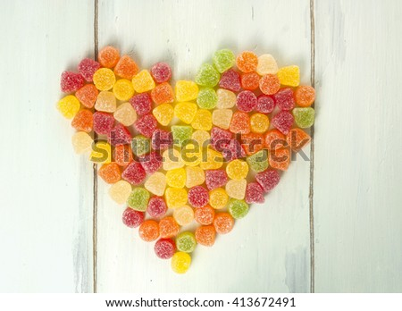 A heart made of many vibrant multicolored gum drops (yellow, red, orange, and green), shot from above on light blue wooden background texture, with copyspace - stock photo