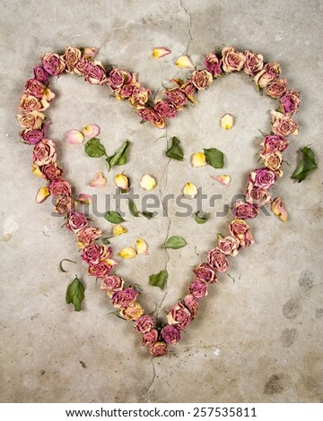 a heart made with old dried up flowers on a textured background - stock photo