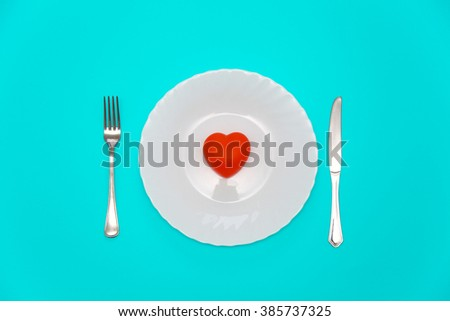 A heart on a white plate with fork and knife from both sides on aquamarine background.