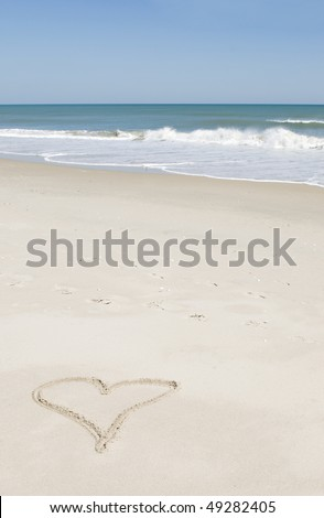 A heart shape drawn in the sand on the beach with ocean an blue sky in background, vertical with selective focus, copy space - stock photo