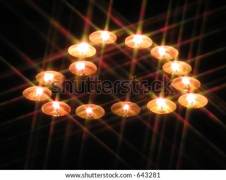 A heart-shaped arrangement of tea-lights through a star filter - stock photo