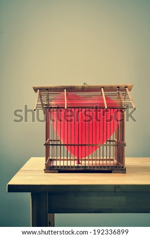 a heart-shaped balloon in an old birdcage, on a table - stock photo