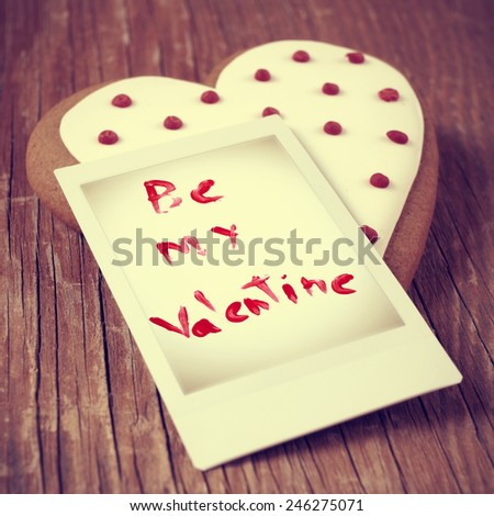 a heart-shaped biscuit and a instant photo with the text be my valentine on a wooden table, with a retro effect - stock photo