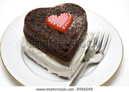 A heart shaped chocolate cake on plate with fork. - stock photo