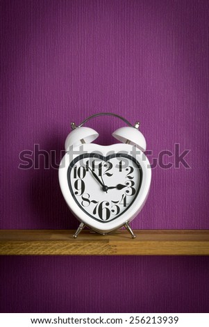 A heart shaped clock on a shelf with purple copy space background - stock photo