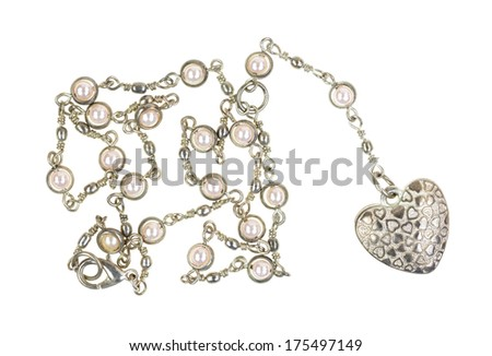 A heart shaped locket on a silver chain with imitation pearls on a white background.
