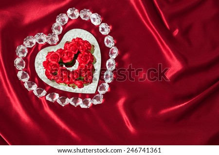 A heart shaped mirror reflects lace and is outlined in gems with a center of red roses in a heart shape. This is all on red satin  draped cloth. - stock photo