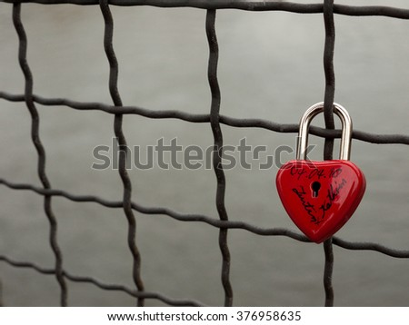 "A heart shaped padlock attatched to wire fence on a bridge. The padlock contains the names ""Justin"" and ""Kathrin"", and the dat 04.04.10 - stock photo"