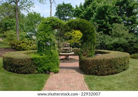 A heart shaped Topiary surrounding a fountain - stock photo