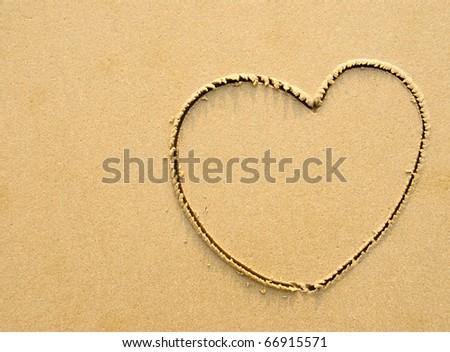 A heart symbol written on a sandy beach - stock photo
