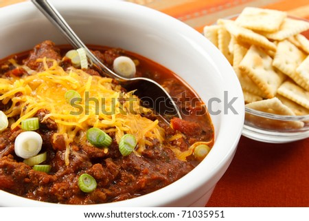 A hearty bowl of chili topped with shredded cheese and scallions makes a tasty lunch or dinner - stock photo