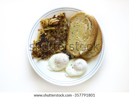 A hearty breakfast with two poached eggs, hash browns and buttered rye toast. - stock photo