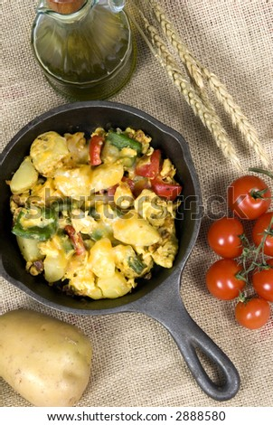 A hearty start to your day with a breakfast skillet of potatoes, eggs, fresh vegetables with melted cheese on top. - stock photo